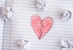 Broken Heart on notebook sheet with some crumpled paper balls on. Broken Heart. Broken Heart on notebook sheet with some crumpled paper balls on it. Close up stock image