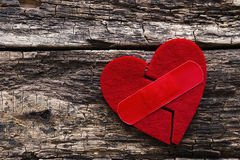 Broken heart with a patch. On a wooden background Stock Image