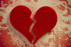 Broken heart. Red broken heart over a vintage painted paper background Royalty Free Stock Photo