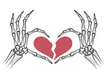 Broken heart in skeleton hands Stock Images