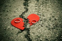 Broken heart with wedding rings on cracked asphalt - divorce concept - stock photo