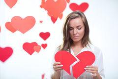 Broken heart. Young girl holding a broken heart royalty free stock image