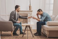 Broken-hearted man feeling awful talking to therapist. Broken-hearted man. Broken-hearted mature men feeling extremely awful talking to helpful professional royalty free stock photography