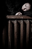 Broken home. Young girl on an old window sill in dirty clothes Stock Photos