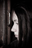 Broken home. Young girl on an old window sill in dirty clothes Royalty Free Stock Photos