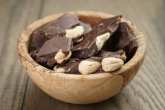 Broken homemade bar of chocolate with cashew nuts in wood bowl Stock Photos
