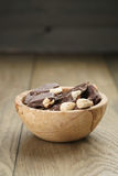 Broken homemade bar of chocolate with cashew nuts in wood bowl Stock Image