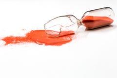 Broken hourglass on white background. Broken glass hourglass with red sand on a white background , time concept Stock Photo