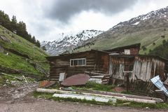 BROKEN HOUSE BEHIND HIGH SNOWY MOUNTAINS royalty free stock photography