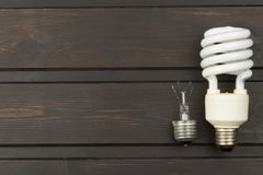 Broken incandescent bulbs and new energy-saving light bulb on wooden background. Stock Photo