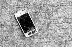 Broken iPhone 4S on asphalt road royalty free stock image