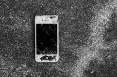 Broken iPhone 4S on asphalt road Royalty Free Stock Images