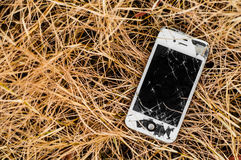 Broken iPhone 4S in dry grass royalty free stock images