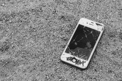 Broken iPhone 4S on sand ground. Broken Apple iPhone on sand with damaged Retina display stock photography