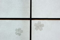 Broken Japanese Shoji sliding door repaired with cherry blossom patches. Broken Japanese traditional Shoji sliding door repaired with cherry blossom patches Royalty Free Stock Photography