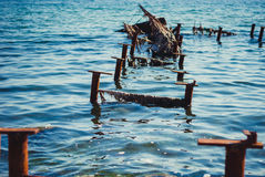 Broken jetty. Fragments sticking out of the sea berth Royalty Free Stock Photos