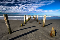 Broken Jetty Looking Out To Sea Old Pilings Left in Sand royalty free stock photo