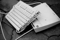 Broken keyboard. White broken keyboard, black and white stock photo
