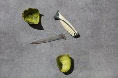 Broken knife and shell of avocado stock photography