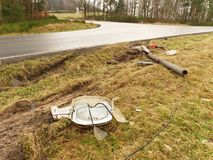 Broken lamp post after car accident. Freeze morning  with slippery asphalt road. January cold and rainy weather Royalty Free Stock Photo