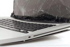 Broken laptop. Broken silver laptop on a white stock photography