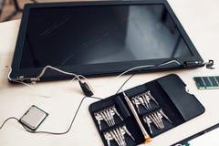 Broken laptop screen with tools set, close-up Stock Photography