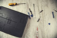 Broken laptop with tools. Broken laptop with different tools on table royalty free stock photos