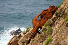 Broken and left. Oxidized rest of a car left in a cliff Royalty Free Stock Image