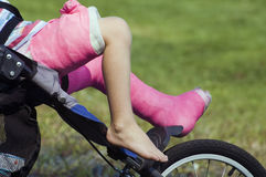 Broken leg. Child with leg in cast in stroller Stock Image