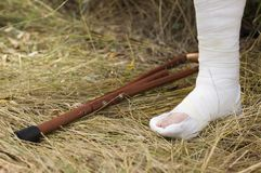 Broken leg in a plaster with crutch Stock Images