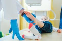 Broken Leg X Ray Scanning. Broken Leg of Little Children X Ray Scanning. Radiology Imaging. Radiologist Preparing Girl for the Scan Stock Photography