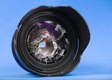 Broken lens. Smashed glass in lens against blue background Stock Photography