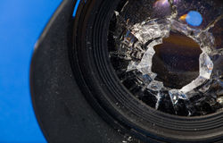 Broken lens. Smashed glass in lens against blue background Stock Photos