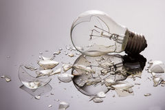 Broken light bulb on shiny surface Stock Photo