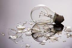 Broken light bulb on shiny surface Stock Photo