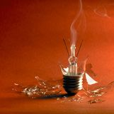 Broken light bulb. Broken upright light bulb with smoke and lots of shards in orange red back Royalty Free Stock Image
