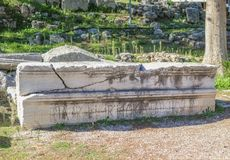 Broken long marble piece of a building carved with Roman letters stacked beside ruins at anicent Corinth near the Temple of Apollo stock photos