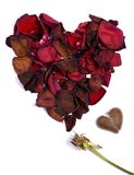 Broken Love 2. The pedals from a withered red rose form a heart... beside it lays a chocolate heart, broken in two.  Lost love Royalty Free Stock Photo