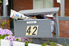 Junk Broke Mailbox. No Junk Mail - wooden post box stuffed with too much mail. Copyspace Stock Photo