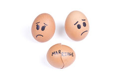 Broken marriage concept. She egg and he egg behind broken egg Stock Photos