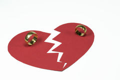 Broken marriage. Red heart shape thorn apart with two golden wedding rings , concept for broken marriage or end of a relationship Royalty Free Stock Photo