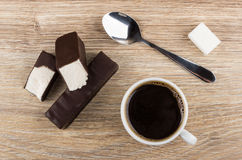 Broken marshmallow in chocolate, coffee in cup, spoon and sugar Stock Image