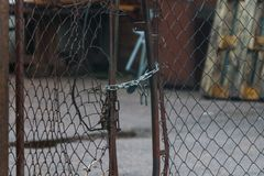 Broken mesh gate with a lock and chain stock images