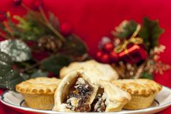 Broken mince pie on a plate with some christmas decorations Royalty Free Stock Images
