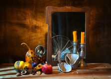 A broken mirror, candles and rotten fruits stock photo