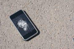 Broken mobile phone on asphalt concept. Background royalty free stock images