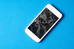 Broken mobile phone with cracked display on a blue background. Broken mobile phone with cracked display on blue background, flat lay royalty free stock images