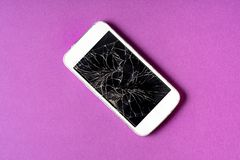 Broken mobile phone with cracked display on purple background. Flat lay stock image