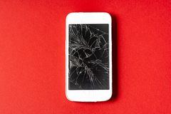 Broken mobile phone with cracked display on red background. Flat lay stock photo