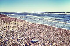 Broken mobile phone on a stony beach. Broken mobile phone with cracked screen on a stony beach, selective focus, color toned picture royalty free stock photo